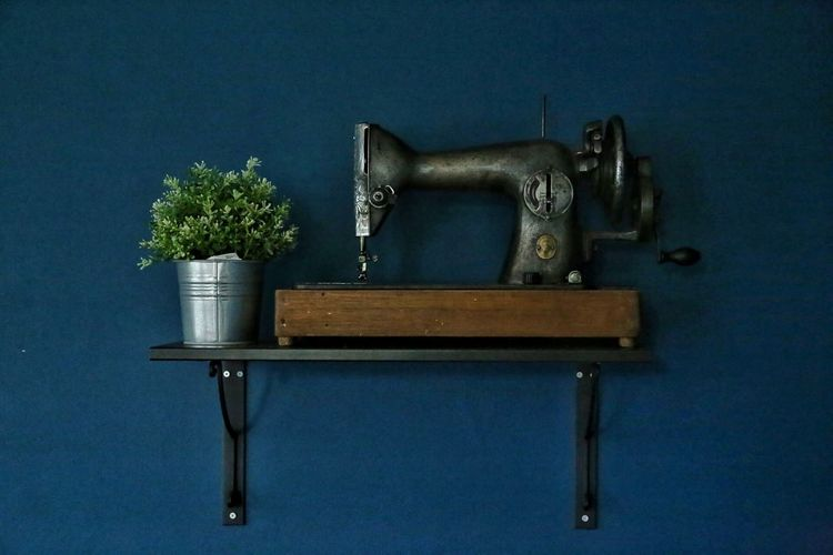 Old Sewing Machine By Potted Plant Over Shelf Mounted On Blue Wall