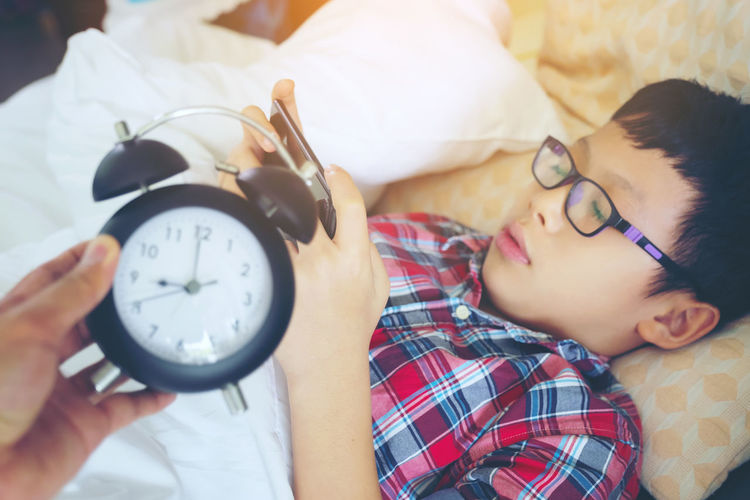 Hand show out for alarm clock on morning, boy playing in the game on the phone lying lazy in bed Bed Boys Child Childhood Clock Furniture Hand Headshot Holding Indoors  Innocence Leisure Activity Lifestyles Lying Down Males  Men One Person Real People Relaxation Time Women