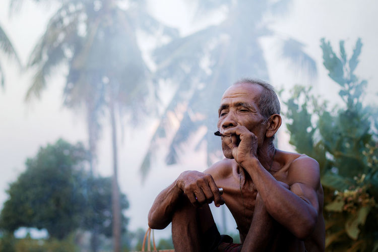 Shirtless senior man smoking cigar against trees