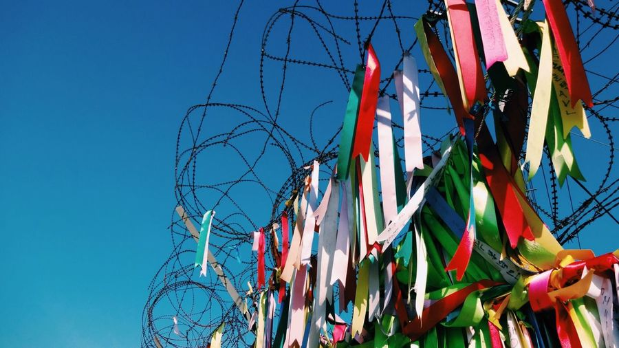 Low angle view of ribbons on barbed wire against clear blue sky during sunny day