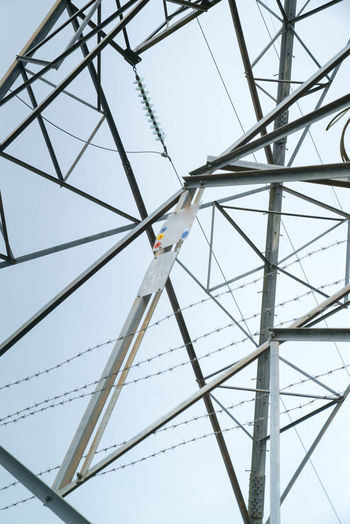 Close-up low angle view of cropped electricity pylon