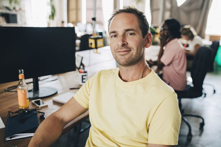 Portrait of confident businessman sitting in creative office