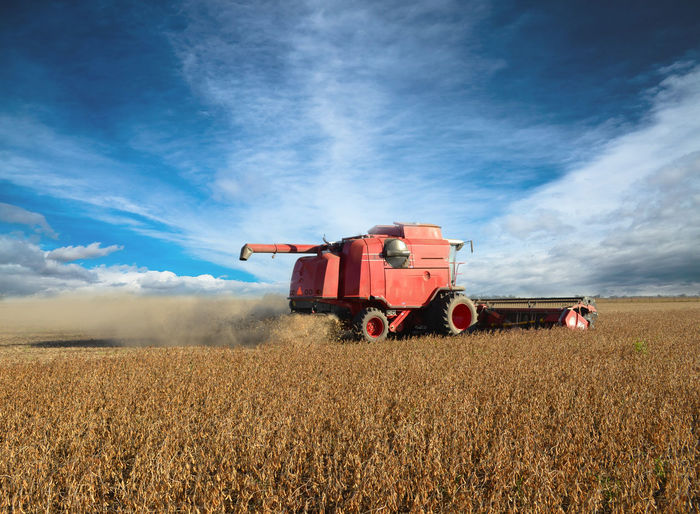 Combine harvester on field against sky