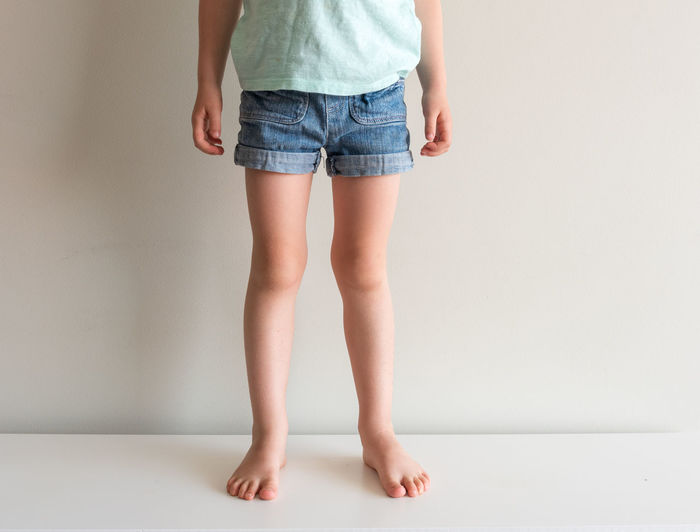 Child's legs in denim shorts One Person Low Section Human Leg Indoors  Standing Body Part Human Body Part Casual Clothing barefoot Front View Studio Shot White Background Lifestyles Shorts Textile Denim Limb Jeans Human Limb Human Foot Child Childhood