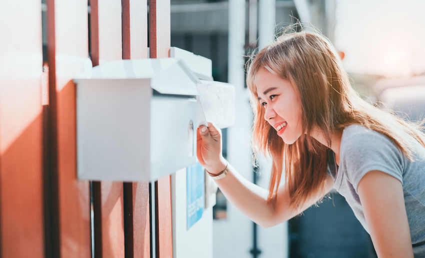 Side view of smiling young woman looking in mailbox
