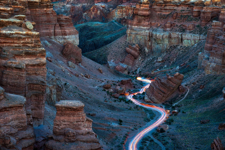 Aerial view of light trails on road amidst rock formations in desert