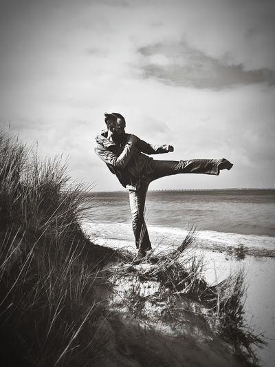 Man exercising on shore at beach