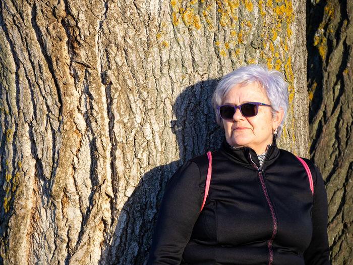 Senior woman standing against tree trunk