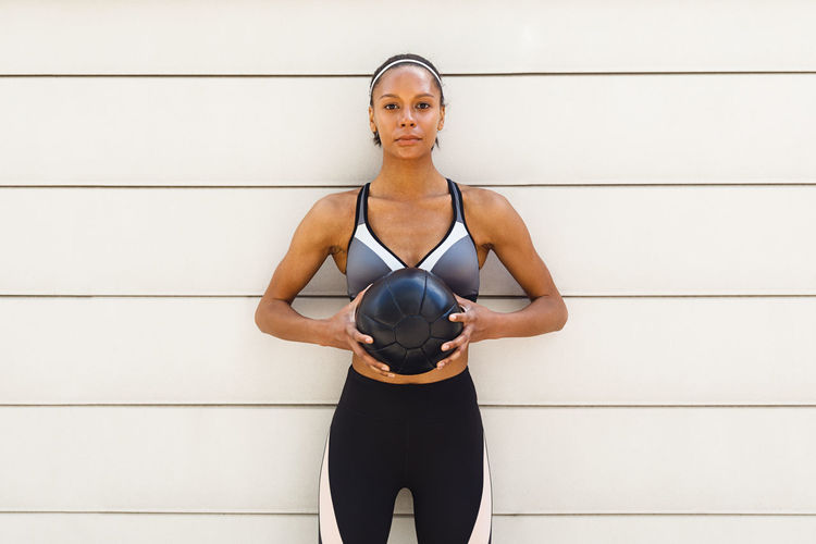 Portrait Of Woman With Medicine Ball Standing Against Wall