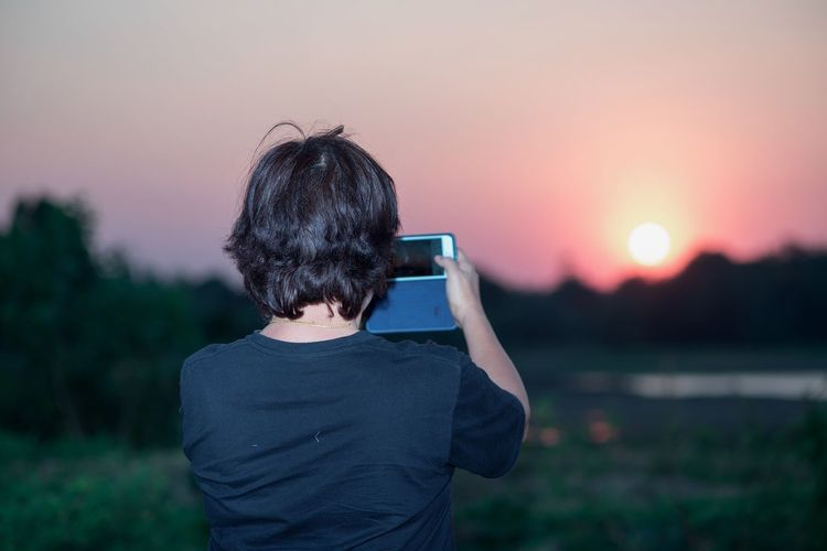 Rear view of man photographing sky during sunset