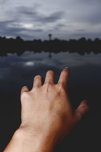 Close-up of hand gesturing against lake