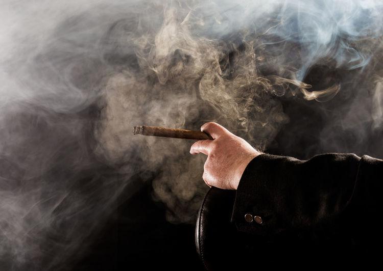 Cropped image of man smoking cigar