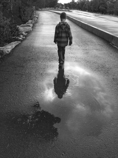 Rear View Of Boy Walking On Wet Footpath During Rainy Season