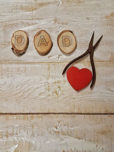 High Angle View Of Dad Alphabets By Pliers And Heart Shape Decoration On Table