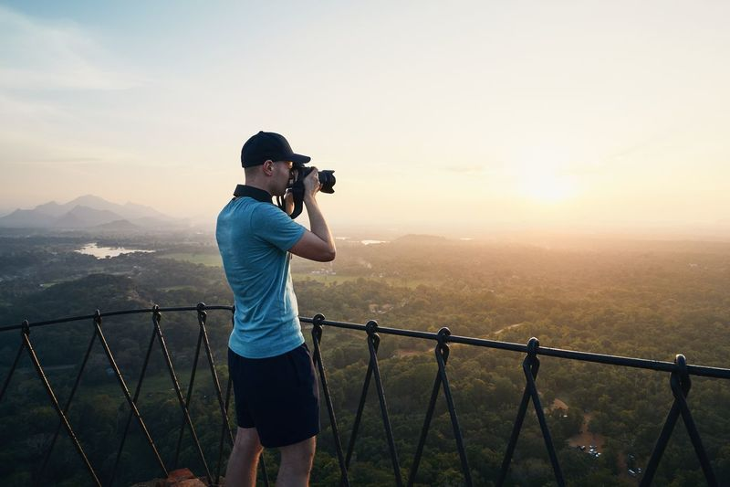 Side view of mid adult man photographing with camera while standing on mountain against sky during sunset