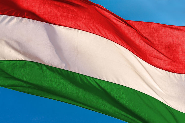 Low angle view of hungarian flag against blue sky
