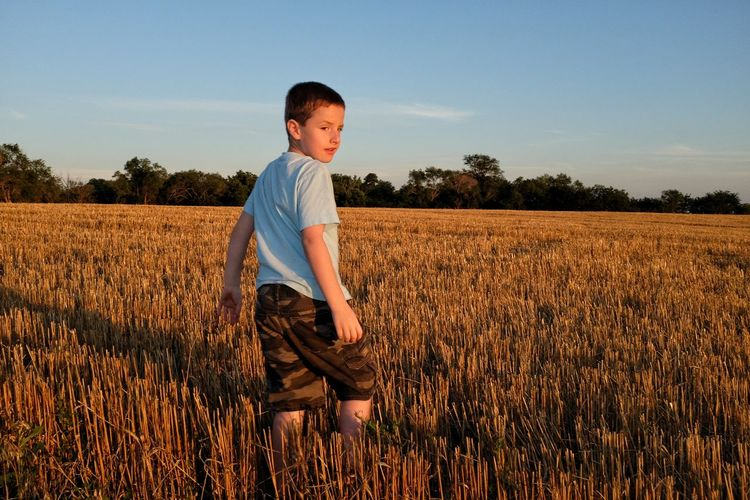 Boy Standing On Field Stubble During Sunset