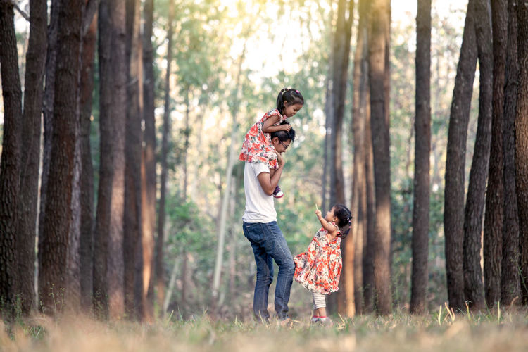 Surface level view of father with daughters in forest