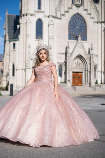 Portrait of beautiful bride wearing crown while standing against church