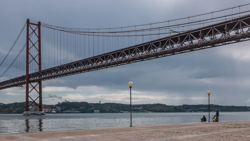 enjoying the view of the Tejo River under the Ponte 25 de Abril bridge Architecture Bridge Bridge - Man Made Structure Bridge Over Water Enjoying Life Enjoying The View Fine Art Photography Meditate Meditation Ponte 25 De Abril Realxing River River View Riverscape Suspension Bridge Suspensionbridge Tejo Tejo River Tranquil Scene Tranquility Travel Destinations Two Persons Walking Around Watching The Sea Watching The Waves