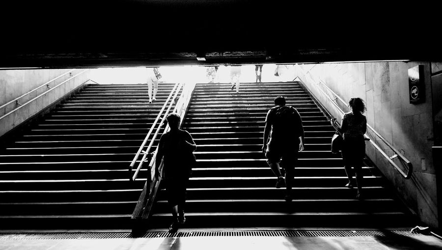 Rear view of people walking on stairs