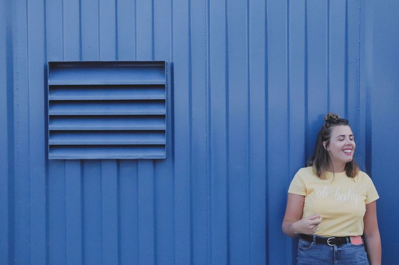 Smiling Young Woman Standing Against Blue Wall