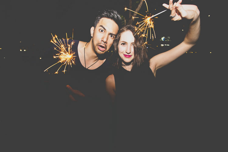 Portrait of couple holding illuminated sparklers at night