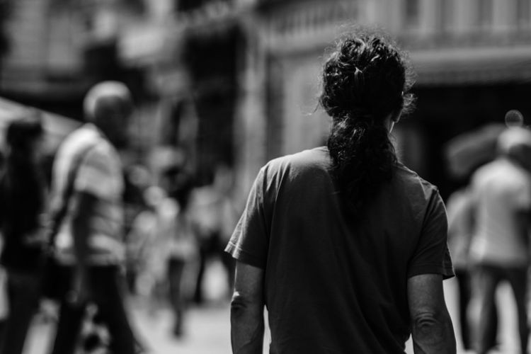 Rear view of man with ponytail standing on street