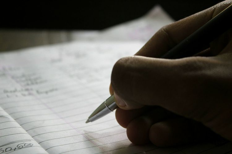 Cropped hand of person writing on book with pen