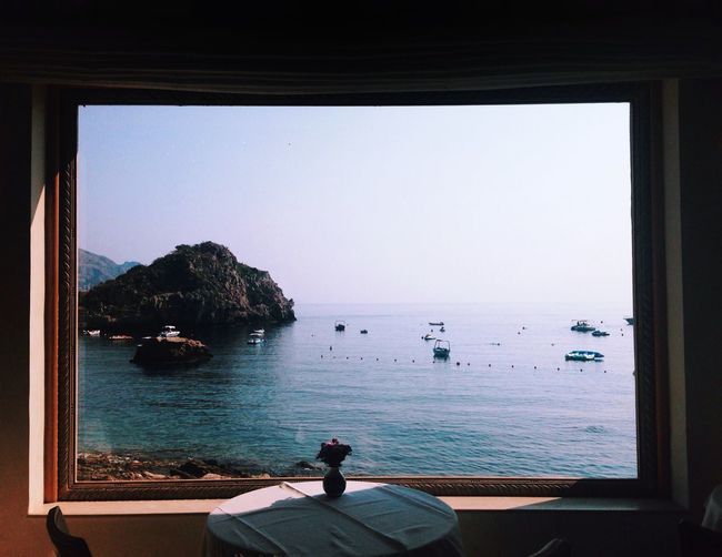 Scenic view of sea against sky seen from window at restaurant