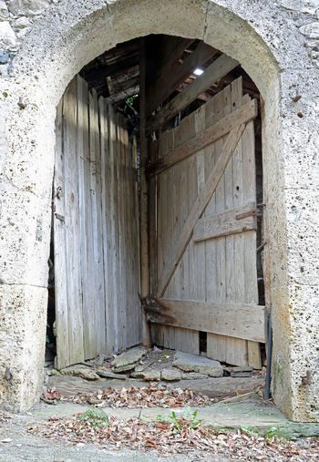 very strange double door of a stable to access two different rooms using a single entrance gate 2 Doppio Gate Wood Access Accessories Arta Terme Carnia Cedarchis Door Double Double Access Double Entrance Entrace Old Rural Scene Stable Stables Strange Two People Wooden