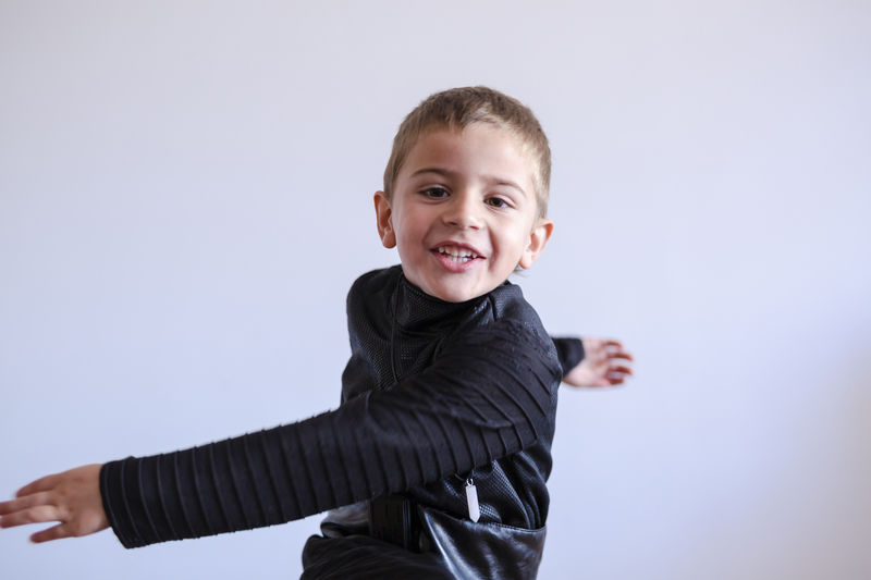 Portrait of smiling boy against white background