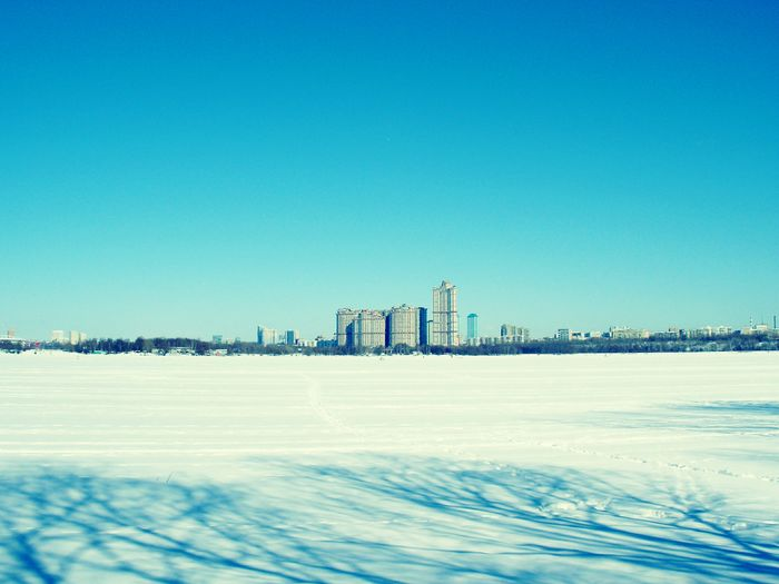 View of city during winter against blue sky