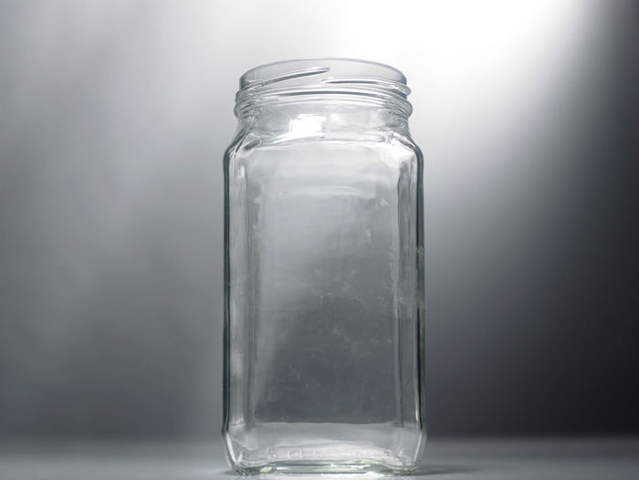 Close-up of empty glass jar against gray wall