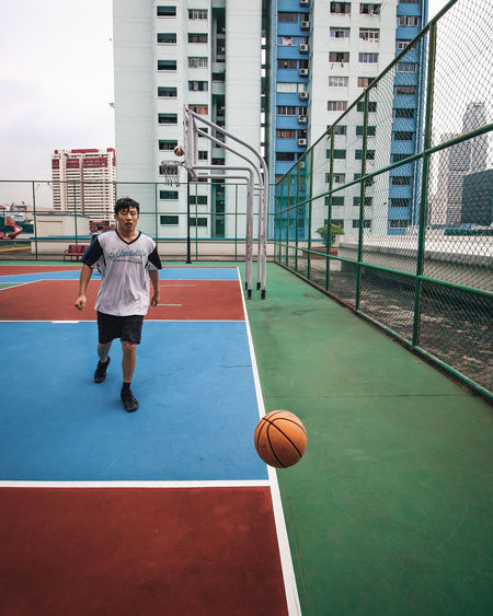 Full length of man playing with ball on basketball court