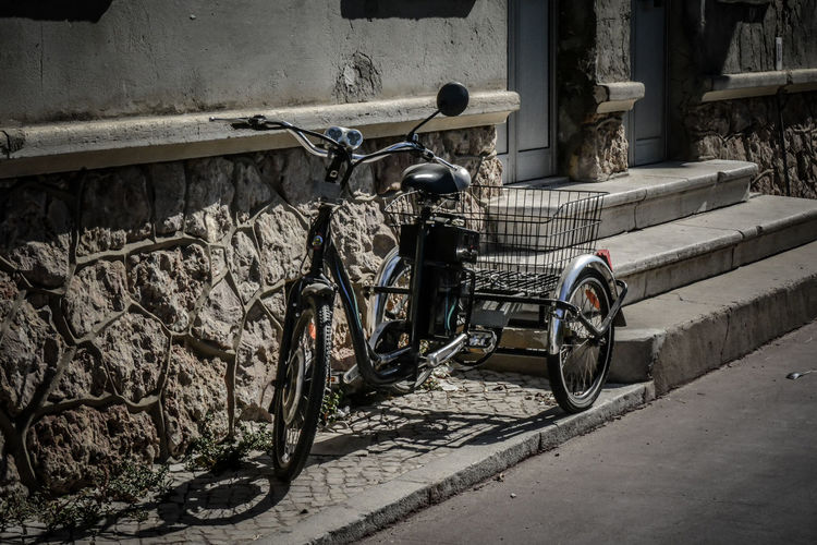 Tricycle On Footpath Outside Building