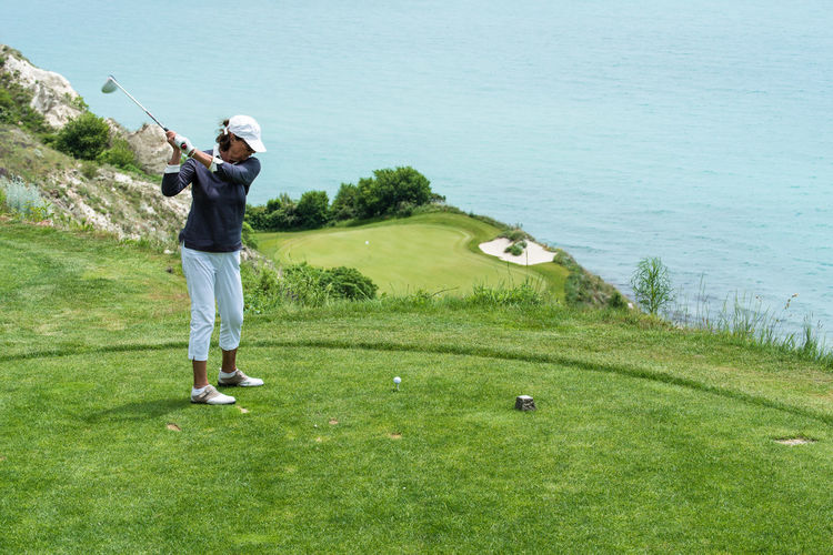 Black Sea Cap Day Golf Golf Ball Golf Club Golf Course Golf Swing Golfer Grass Green - Golf Course Leisure Activity Lifestyles Motion One Person Outdoors Playing Spectacular Sport Standing Taking A Shot - Sport Tee Thracian Cliffs Golf Course Weekend Activities Woman Summer Sports