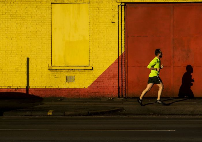 Running Man. Lifestyles One Person Running Streetphotography Photography Wallpainting EyeEm Gallery Eyeemphoto EyeEm Best Shots Taking Photos Narratives Art Cities Subjective Colours Wall Colourfull Yellow Red Photographer Colours And Patterns For The Love Of Photography Light