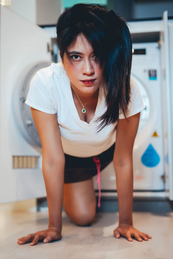 Woman coming out from washing machine at home