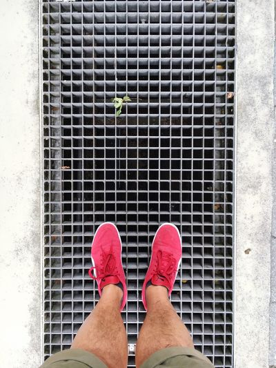 Low section of man wearing red shoe standing on sewer