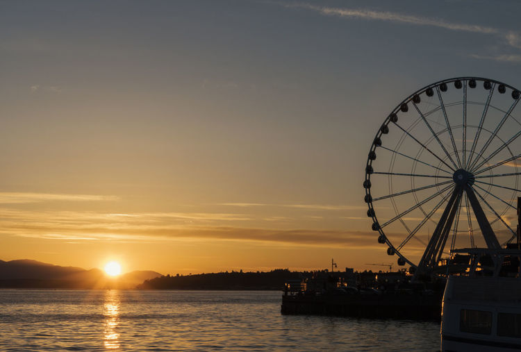 Seattle waterfront at sunset with Great wheel Ferris wheel with sunburst. Elliott Bay Seattle Sky And Clouds Sunburst Tourist Attraction  Travel Amusement Park Amusement Park Ride Arts Culture And Entertainment Cruise Ferris Wheel Fine Art Golden Hour Lens Flare Nature No People Orange Color Outdoors Sky Sunset Tourism Transportation Vacation Water Waterfront