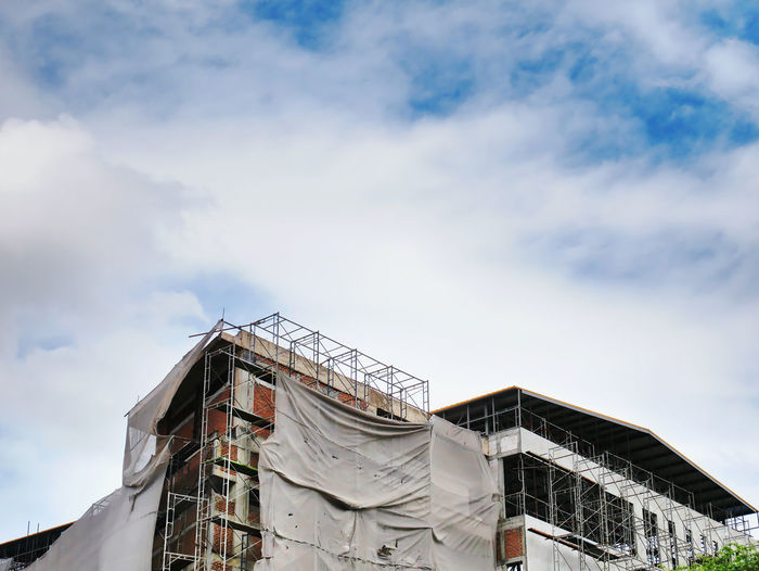 Large under construction building with frames and covers against cloudy blue sky