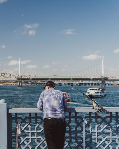 A fisherman stands on the bridge waiting for a fish to bite in Istanbul. - IG: @LostBoyMemoirs (All photos taken on Sony A6300 and edited in Lightroom). Istanbul Turkey Turkish EyeEm Best Shots The Week on EyeEm Streetwise Photography Streetphotography Street Photography People People Watching people and places Travel Water Real People Railing Lifestyles Nature Bridge Nautical Vessel Cloud - Sky Fishing Fisherman The Art Of Street Photography