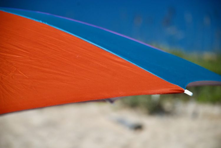 Close up of red and blue beach umbrella