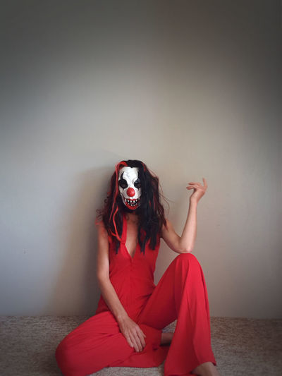 Woman dressed in red wearing scary clown mask