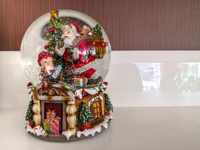 Snow globe with child and Santa Claus on a white board Snow Globe Snowing Snow Santa Claus Child Christmas Glass Sphere Indoor Atmosphere Advent Season  Christmas Season Holy Night Decoration Celebration Xmas Gift Presents Christmas Decoration Christmas Celebration Red christmas tree Tradition Christmas Present
