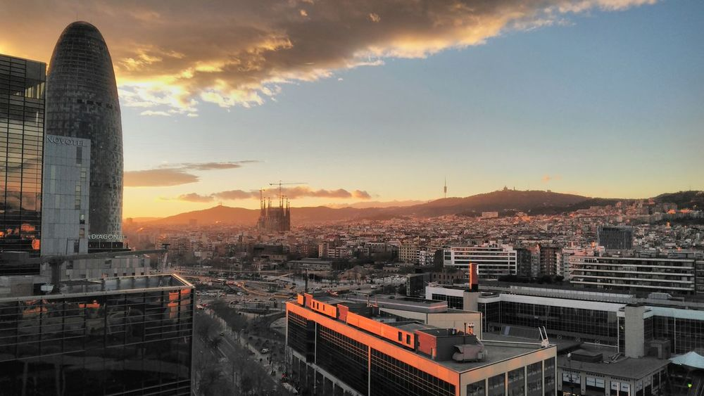 Cityscape City Urban Skyline Architecture Sunset Sky Skyscraper Building Exterior No People Outdoors Agbar Tower Sagrada Familia Barcelona Nouvel sunset #sun #clouds #skylovers #sky #nature #beautifulinnature #naturalbeauty photography landscape Travel Destinations Dusk High Angle View Business Finance And Industry Aerial View Day
