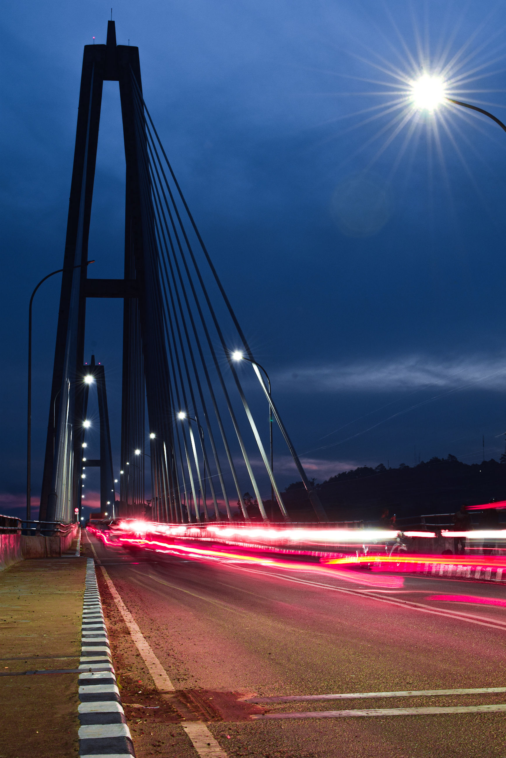 illuminated, transportation, sky, road, night, architecture, city, long exposure, built structure, motion, connection, street, bridge, light trail, speed, nature, street light, lighting equipment, bridge - man made structure, no people, lens flare, the way forward, outdoors