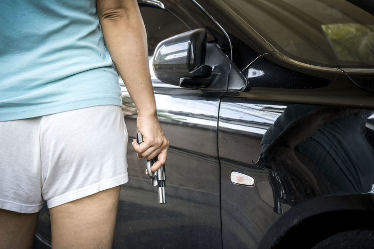 Midsection Of Woman Holding Gun While Standing By Car