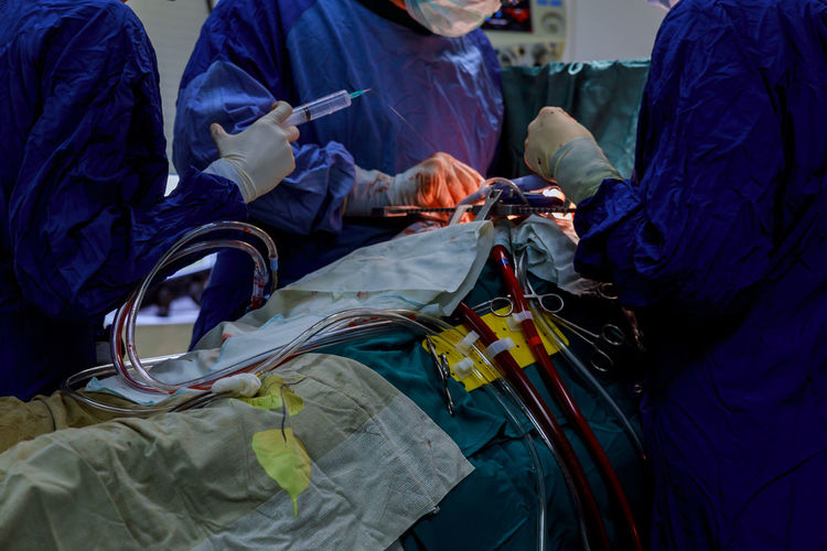 Midsection Of Doctors Operating Patient In Hospital